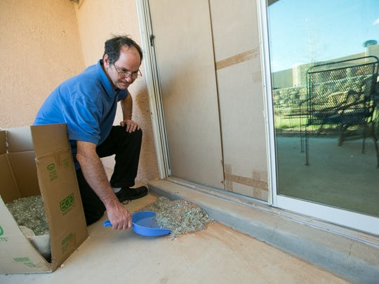 Donald Porter, of Las Cruces, clean up glass on March 9, 2016, that was left behind after a stray bullet shattered the sliding door and tore through a his nephew's playpen on Sunday March, 6, 2016. There were no injuries and foul play was not suspected.
