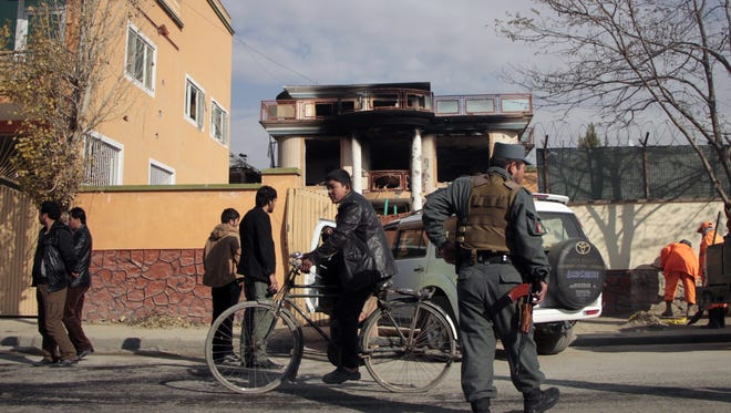 Afghans pass by the office of the unidentified aid group a day after an attack by Taliban militants, in Kabul.