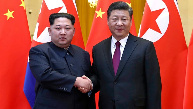 In this photo, provided by China's Xinhua News Agency, North Korean leader Kim Jong Un (left) shakes hands with Chinese President Xi Jinping (right) during their meeting in Beijing.