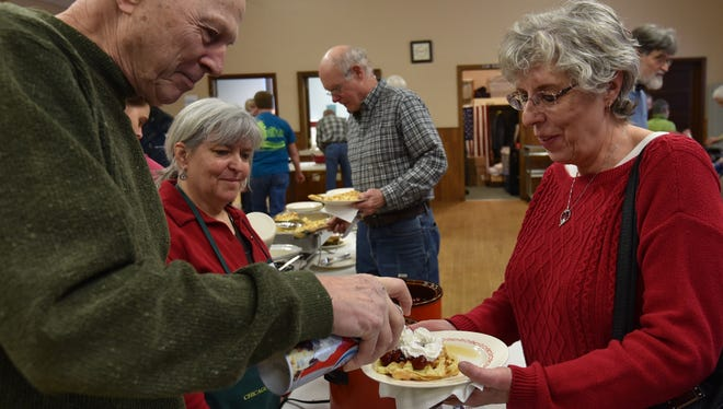 Jim Jauquet adds the whipped cream to Joanne Hersam's cherry-topped waffles at a past Great Waffle Breakfast held by The Ridges Sanctuary.