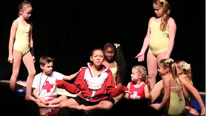 "Micah Nalzaro (Santa) and city of Vero Beach gymnastics students star in the 2015 production of ""Santa Who?"""