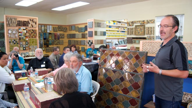 Syzygy Tile show room manager Patrick Hoskins greets the Silver City/Grant County Chamber of Commerce members on Thursday. Hoskins led the Chamber members on a tour of the tile company, which was founded in 1993 and which creates hand made tile.