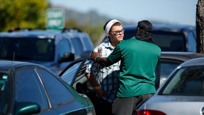Student Mathew Downing, left, is comforted by an unidentified man as they return to Umpqua Community College Monday, Oct. 5, in Roseburg, Ore.