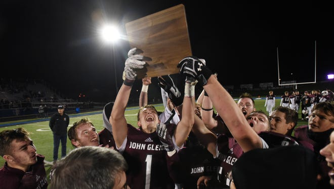 John Glenn gathers around the Division IV Regional Championship trophy at Zanesville High School on Friday after defeating Muskingum Valley League rival Philo.