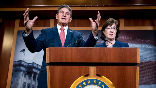 Sen. Joe Manchin, D-W.Va., left, accompanied by Sen. Susan Collins, R-Maine, right, speaks at a news conference on Capitol Hill in Washington, Jan. 22, 2018, after Senators reach an agreement to advance a bill ending government shutdown.