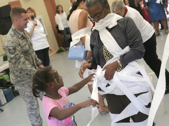 Garnetta Pender is wrapped by Trinitee, 7, in a mummie contest during the Safe Summer Fridays event at North Lake Park.