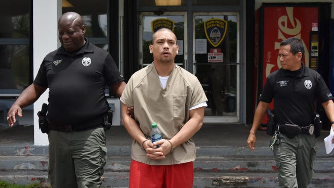 In this July 6 file photo, Peter Gines is escorted out of the Guam Police Department HagŒåtña precinct by Department of Corrections officers.