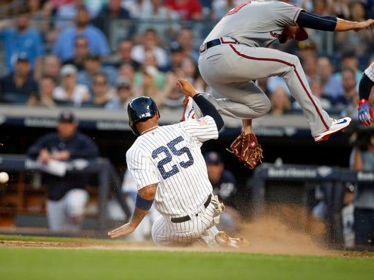 New York Yankees second baseman Gleyber Torres (25) scores a run on wild pitch.