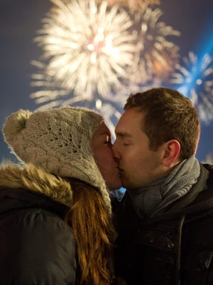 A couple kiss as fireworks illuminate the night sky over the Brandenburger Tor to welcome in the new year in Berlin.