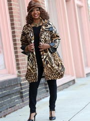 Maxine Lewis wears a black and brown animal print Design Today swing jacket with faux leather detailing on the collar and sleeves.