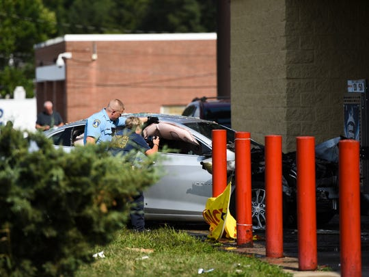 Members of the Lansing Police and Lansing Fire Department take photos of a car pulled from the entrance of the Family Dollar in the 900 block of W. Holmes, Saturday afternoon, Aug. 4, 2018, after it crashed into the front entryway of the store.