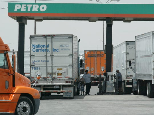 Long-haul truck drivers fill their tanks with diesel