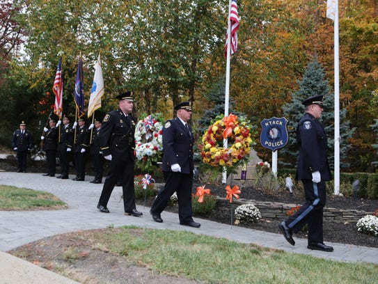 Police officers walk past the memorial after placing