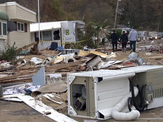 People walk through debris at the Paradise Park mobile