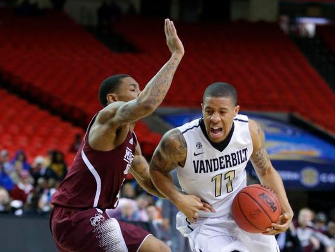 Vanderbilt Commodores guard Kyle Fuller (11) drives the ball against Mississippi State Bulldogs guard Trivante Bloodman (4) in the first round of the SEC Tournament at Georgia Dome. Mississippi State won 82-68.