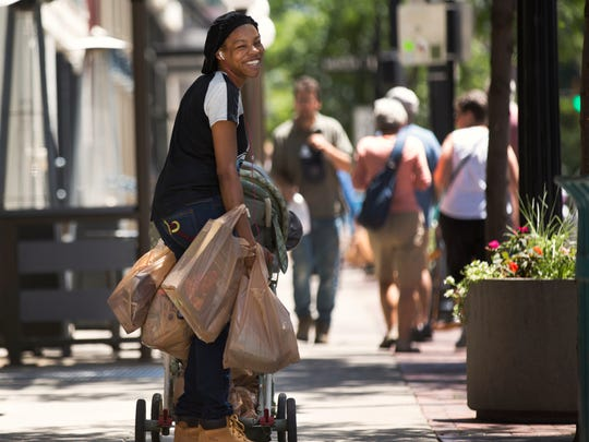 DeAsia Clark, 24, heads home from the Vine Street Kroger with her 4-month-old son, Jonathan. Clark, who works at DHL, lives on Ninth street in Over-the-Rhine. When the new Kroger opens at Court and Walnut streets in 2019, it will actually be closer to her, but she worries about older OTR residents who will have to travel further.
