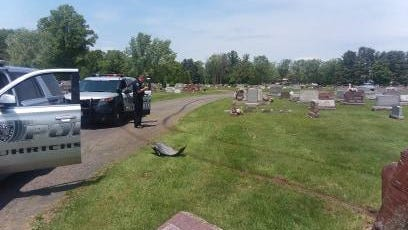Uhrichsville police look over damage Tuesday caused by a vehicle in Union Cemetery.