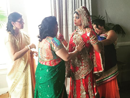 The bride Manisha getting dressed by her mom, aunt,