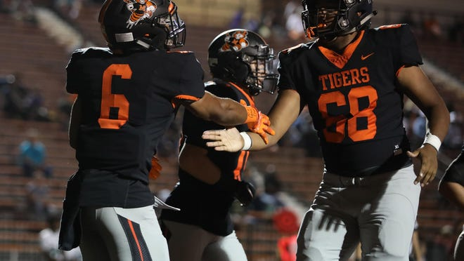 Massillon's Terrence Keyes (6) is congratulated by teammate Terrence Rankl after a first-quarter touchdown in the Tigers' 2019 win over Firestone. Rankl is one of three current Massillon players committed to FBS Division I programs.