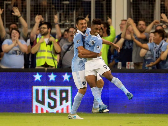 Sporting Kansas City forward Latif Blessing (9) celebrates his goal with teammate Roger Espinoza, left, during the first half in the final of the U.S. Open Cup soccer tournament against the New York Red Bulls in Kansas City, Kan., Wednesday, Sept. 20, 2017. (AP Photo/Orlin Wagner)