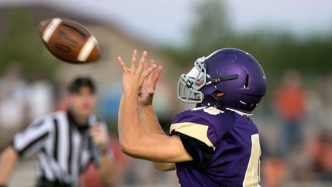 Queen Creek High receiver Skyler Bollman makes a catch for a touchdown against Poston Butte during the first half of the high school football game at Queen Creek High on Friday, Aug. 22, 2014.