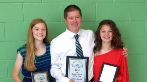 Reynolds girls soccer players Megan McCallister, left, and Zoe Lewis with Rockets coach Patrick Gladys.