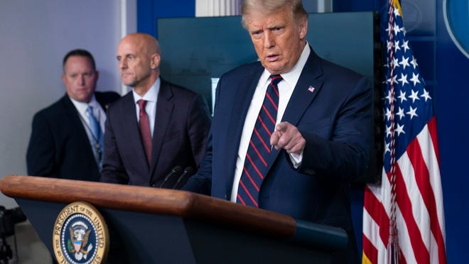 President Donald Trump, accompanied by Food and Drug Administration Commissioner Dr. Stephen Hahn, speaks during a media briefing Sunday in Washington.