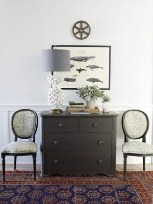 The symmetrical layout of chairs on either side of a cabinet is echoed by the symmetrical arrangement of images in the framed print above, creating an orderly and calming look.