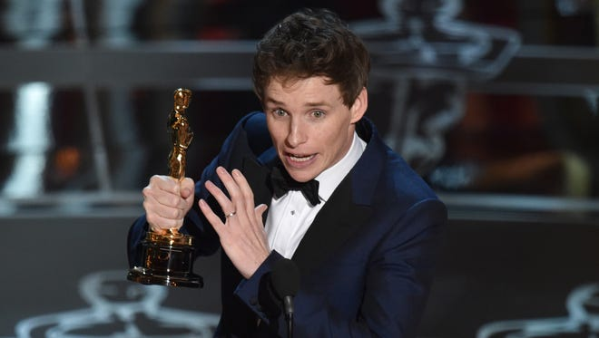 """Eddie Redmayne accepts the award for best actor in a leading role for """"The Theory of Everything"""" at the Oscars on Sunday, Feb. 22, 2015, at the Dolby Theatre in Los Angeles."""