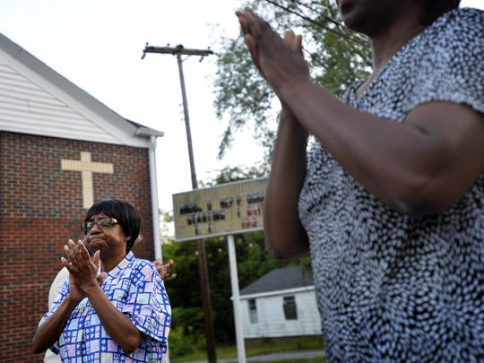 Barbara Powell, middle, a member of the City View Community Coalition, prays during a prayer on Morgan Street in the heart of City View on Wednesday, July 15, 2015. She and the rest of the group prayed loud and proud as they walked in hopes to take back their streets.