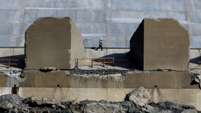 A worker walks along the lower end of the Oroville Dam spillway on Thursday in Oroville. California water officials and the construction manager said Thursday that recently found hairline cracks on the spillway are normal and expected in reinforced concrete because it shrinks as it cures.
