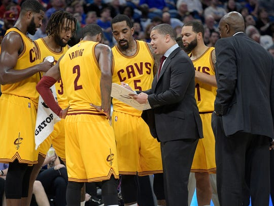 FILE - In this March 11, 2017, file photo, Cleveland Cavaliers head coach Tyronn Lue, center, talks to his players during a timeout in the second half of an NBA basketball game against the Orlando Magic in Orlando, Fla. Lue would prefer less attention, but it comes with the territory as coach of the defending NBA champions. Lue is back in the NBA Finals, and the Cavaliers acknowledge they probably wouldn't be in position to win another title if not for Lue's calming influence. (AP Photo/Phelan M. Ebenhack, File)