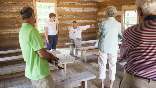 Justin Reiter, center, executive director of the American Frontier Culture Foundation, talks to visitors at the newly reconstructed Mount Tabor Church after a dedication ceremony at the Frontier Culture Museum on Saturday.