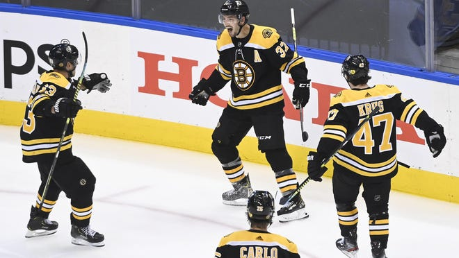 Boston Bruins center Patrice Bergeron (37) reacts with teammates Brad Marchand (63) Torey Krug (47) and Brandon Carlo after scoring the game-winning goal against the Carolina Hurricanes during the second overtime period Wednesday in Toronto.