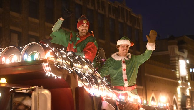 People on the Beaver Island Brewing float wave to the crowd during the 2015 Winter Nights & Lights parade in downtown St. Cloud.