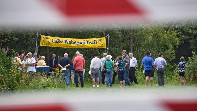 People gather near a barricade on an existing section of trail before the start of a groundbreaking ceremony for the Lake Wobegon Trail extension Tuesday, Aug. 22, at River's Edge Park in Waite Park.