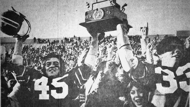 Franklin's Jim Casey and Tim Hollandsworth hoist the 1975 Class A championship football trophy.