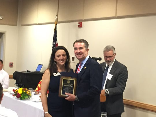 Gov. Ralph Northam presents the Distinguished Service award to Wanda Caffrey at the Eastern Shore of Virginia Chamber of Commerce annual meeting on Monday, July 23, 2018 in Melfa, Virginia.
