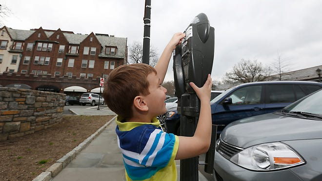 Jonah Vardi, 4, from Scarsdale, feeds the parking meter in downtown Scarsdale on  March 25.