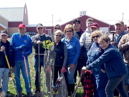 Manitowoc Sunrise Rotary recently planted 23 trees, one for each of their members, at Farm Wisconsin Discovery Center in Newton. Pictured are Rotary members, family members and two Manitowoc Lincoln High School students who helped with the effort.