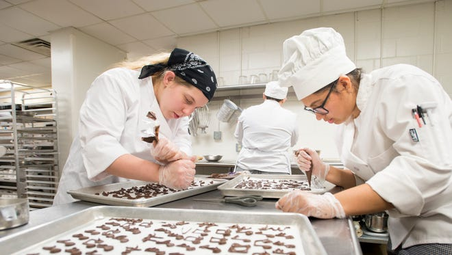 "Culinary and Hospitality Club members Tatyana Hulsey, left, and Ciara Silva create chocolate notes for the upcoming Choral Society of Pensacola's ""A Toast to Summer"" as they prepare food for the event at Pensacola State College on Tuesday, June 20, 2017."