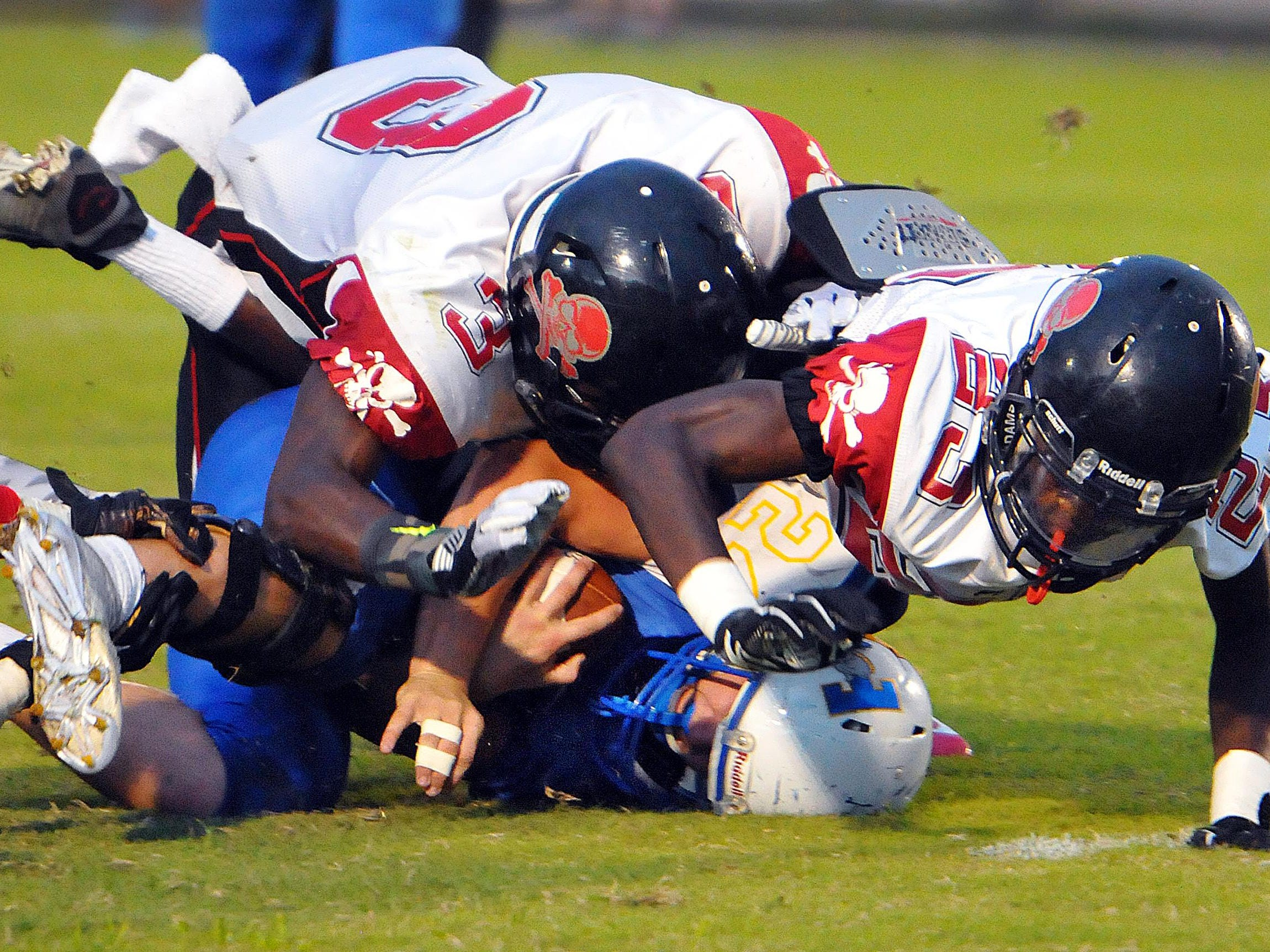 Titusville High's Jacob Farris (24) is tackled on a return by Palm Bay High's Desmond Arthur (3) and Ozzie Samuel (23) during Friday night's game at Titusville High School.