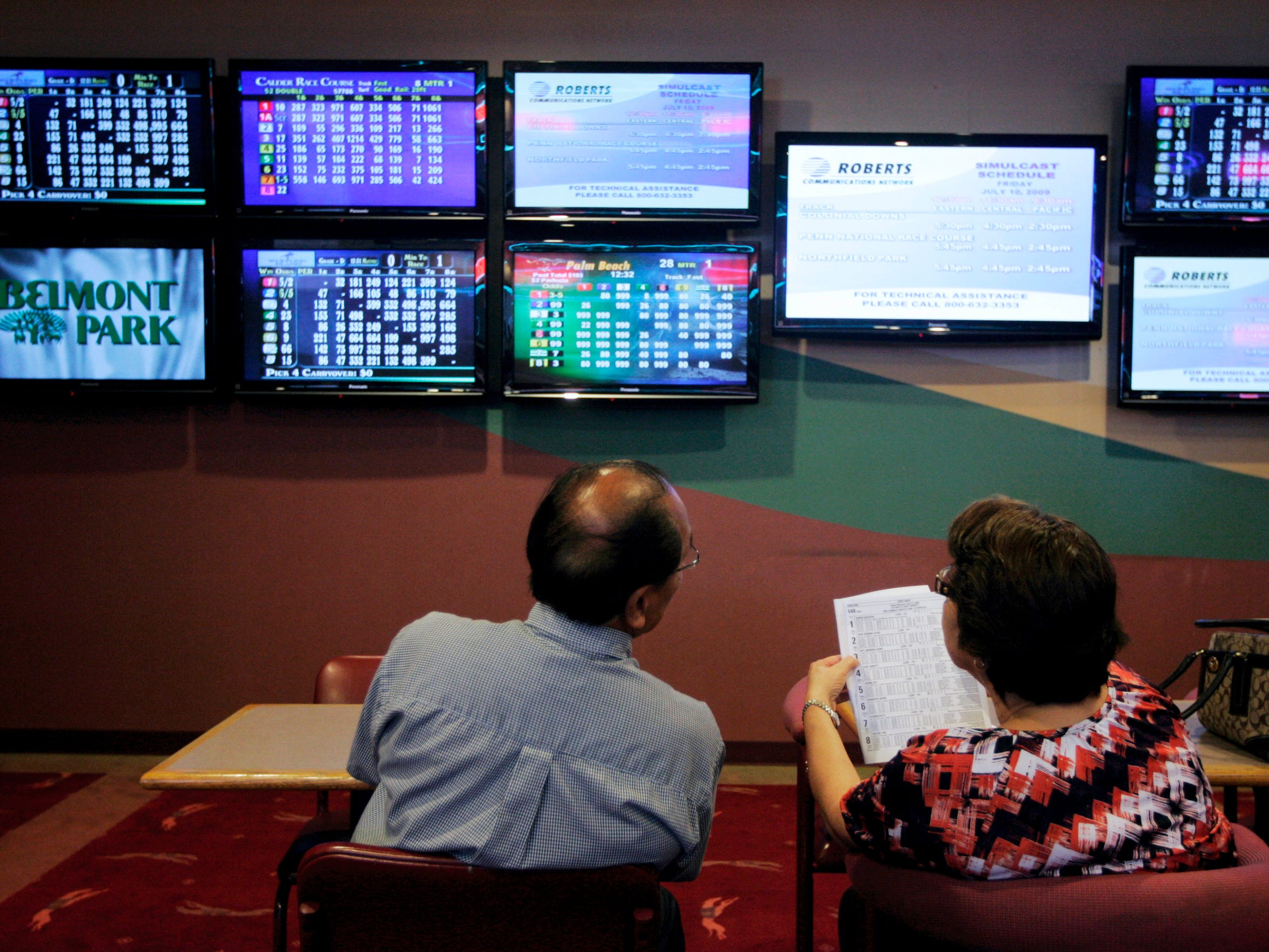Floro and Mary Ramos look over the racing forms as they watch the races on flat-screen TVs Friday, July 10, 2009 at the Gulf Coast Racetrack in Corpus Christi. Track owners and managers held a ribbon cutting ceremony for the newly reopened facility Friday, where simulcast horse and greyhound betting is available.