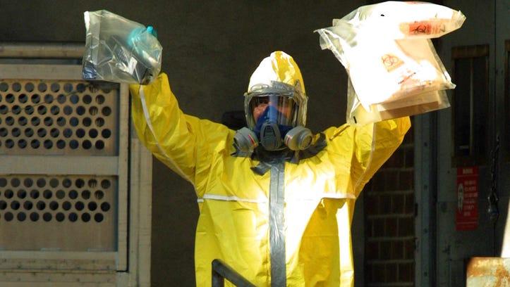 An investigator wearing a hazardous materials suit