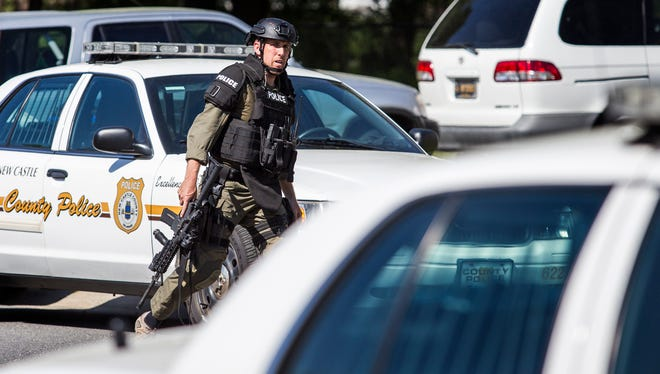 A SWAT officer rushes to a staging area on Freedom Trail in a standoff with a man who, according to a source close to the investigation, was threatening to kill himself after killing his girlfriend on Tuesday afternoon.
