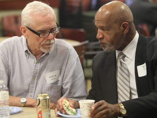 Steve Jarose, left, and Ray Scott chat after Thursday's Unite Rochester progress report meeting at the Democrat and Chronicle.