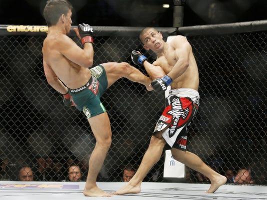 Joseph Benavidez kicks John Moraga during their flyweight mixed martial arts bout at UFC 187 Saturday in Las Vegas.