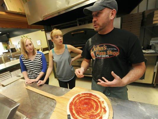 John Navratil, owner of John's Pizza Shop in York Township, explains pizza preparation to Flipside crew Abbey Zelko, left, and Ashley May on Thursday, Oct. 1, 2015.  Jason Plotkin - York Daily Record/Sunday News