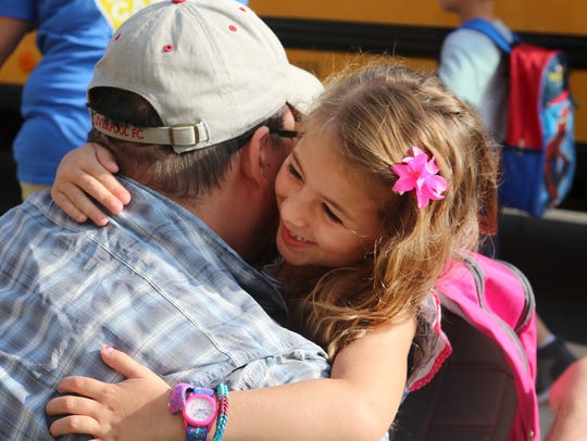 Kindergartner Savannah Ayton hugs her father, Jordan Ayton, at the J. Ralph McIlvaine Early Childhood Center in Magnolia, where kindergartners were starting their first day of school.