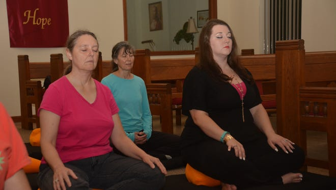 Sherry Bovey, from left, Linda Bourgault and Charissa Inabnet meditate at First Christian Church in Pineville.